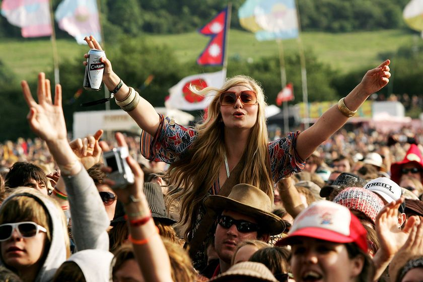 female festival goer holding beer can on mans shoulders in crowd