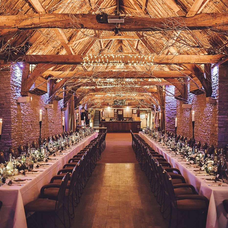 barn wedding reception long row of table beamed ceiling