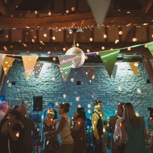 people dancing under bunting and fairy lights in barn