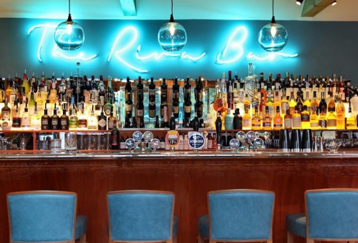 blue neon sign above wooden bar with shovels of alcohol hanging ceiling lights