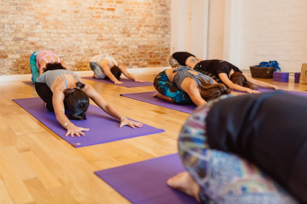 yoga class stretching on floor in studio