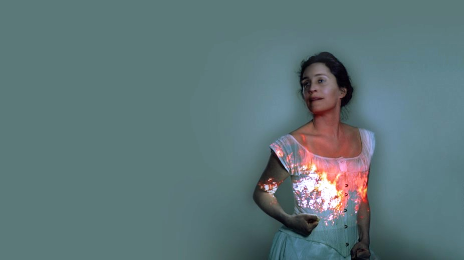 lady in white dress with fire light reflected on her