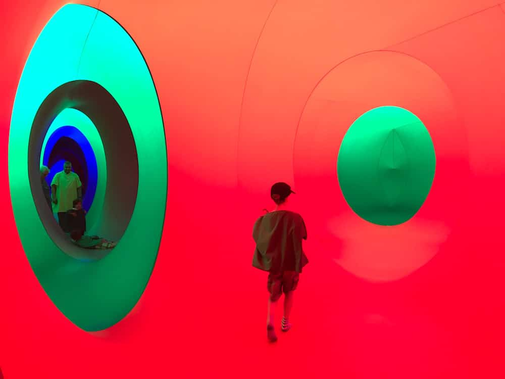 child running through multicoloured tunnel