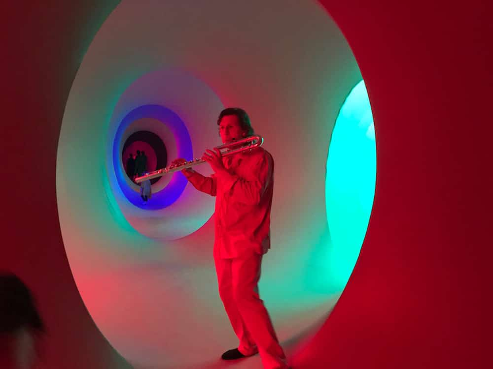 man playing flue in multicoloured light tunnel