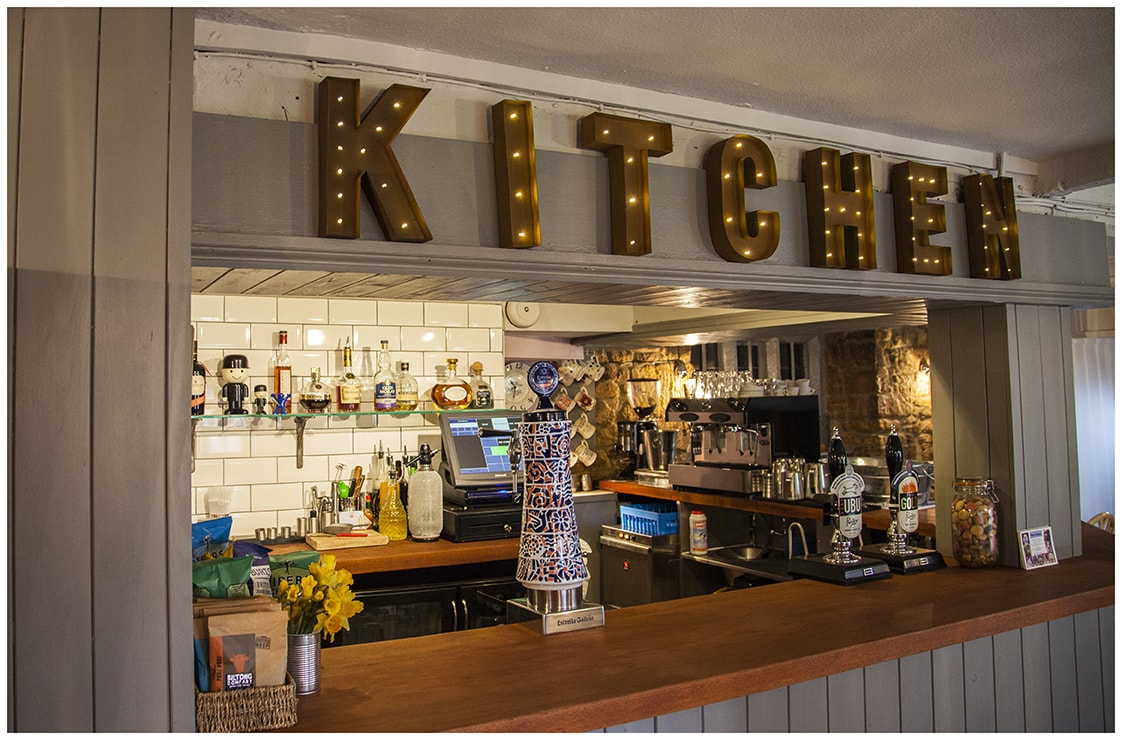 kitchen letters above bar with shelves of alcohol