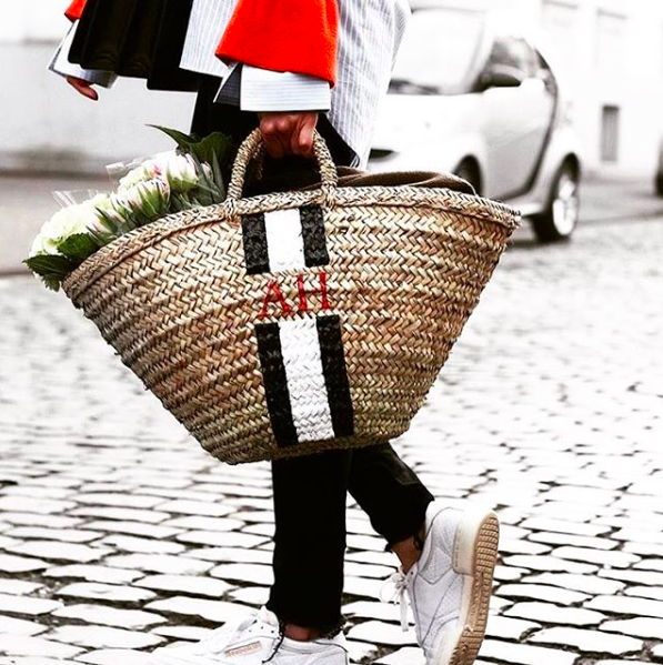 woman holding wicker basket containing flowers on cobble road