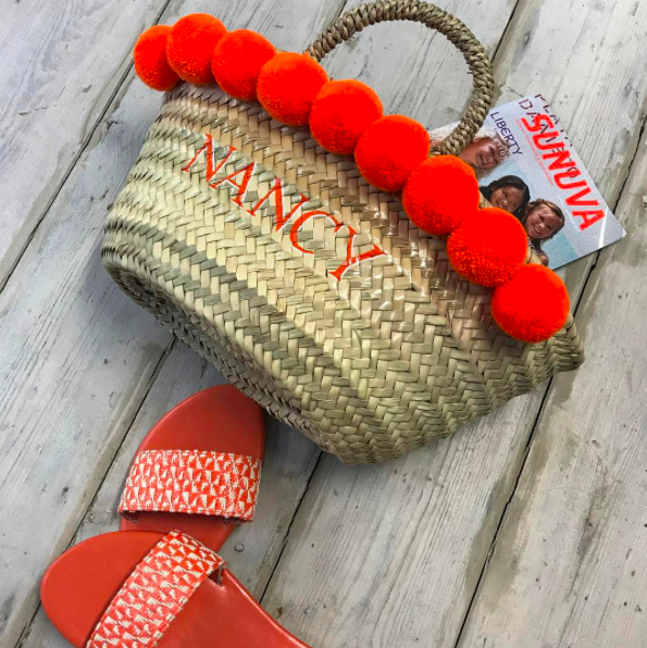 wicker basket orange pom noms orange sandals on deck floor