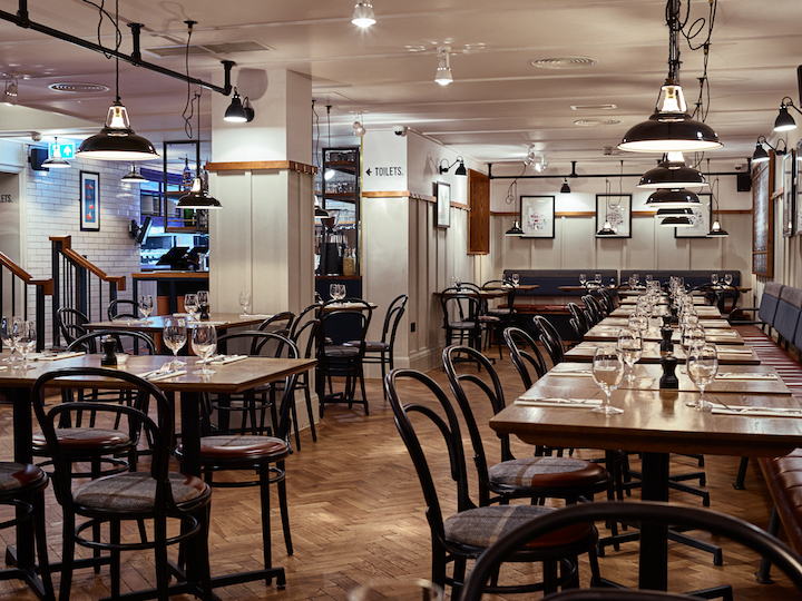 restaurant tables with industrial lighting with white butchers tiles