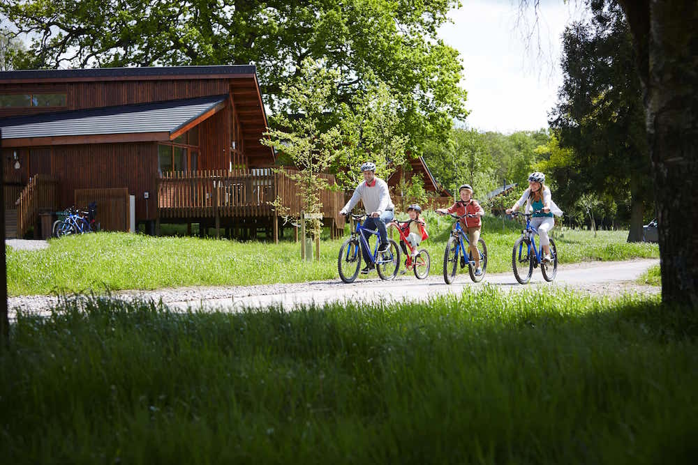 family riding bikes past trees log cabin