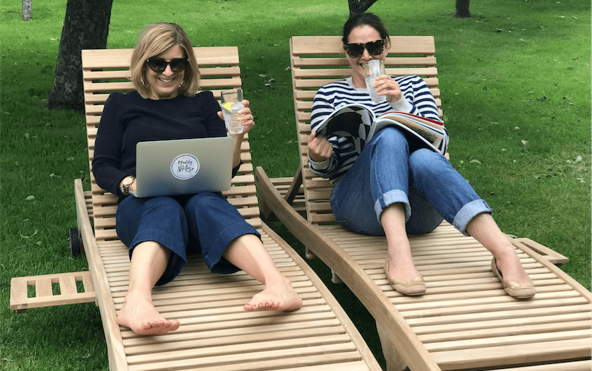 two ladies on deck chairs on grass on laptop reading magazine drinking gin