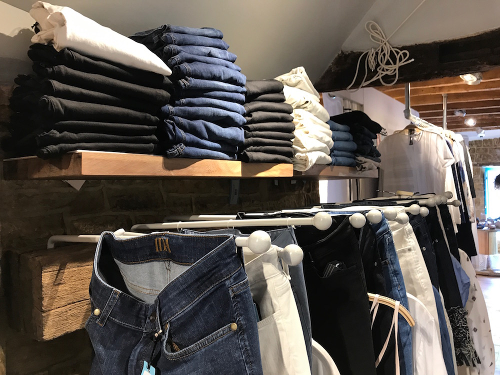 shelve of women's jeans above rack of hanging jeans