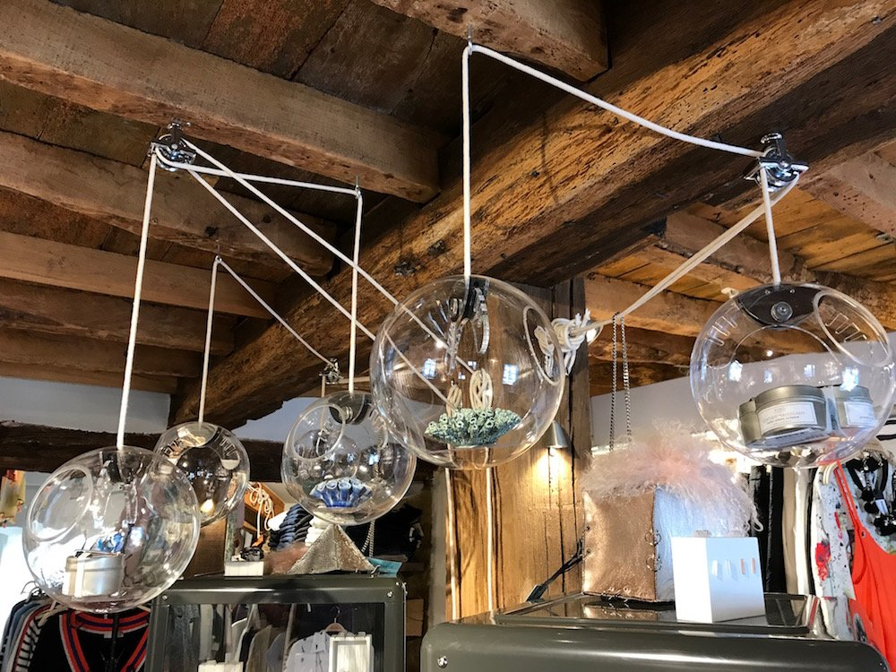 glass balls containing products hanging from ceiling