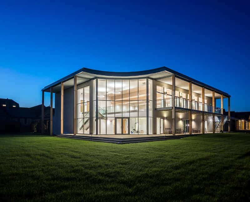 summerfield modernist glass building lit up at night