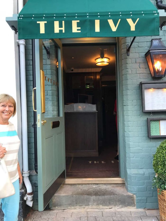 lady smiling at the ivy entrance green door