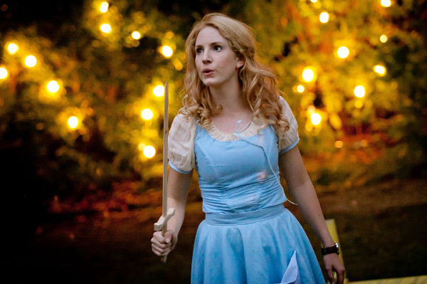 blonde lady in blue dress holding wooden sword