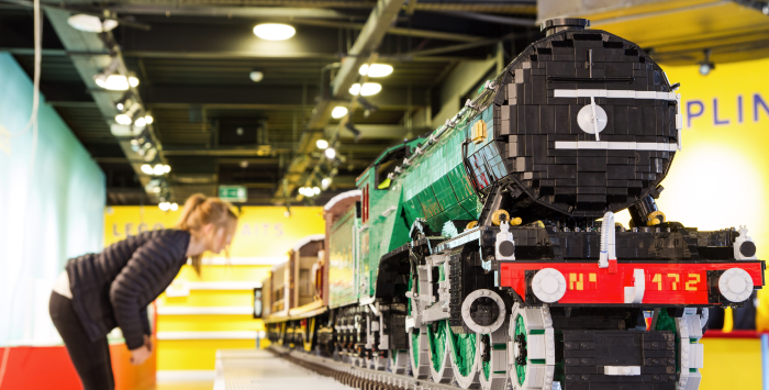woman looking at big lego train