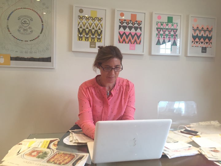 lady in pink shirt and glasses working on Macbook