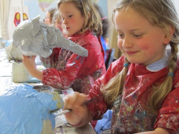 two young girls in messy aprons doing crafts