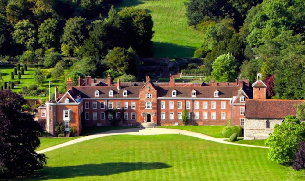 grand red brick Manor House surrounded by trees