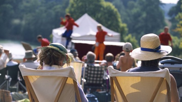 audience watching outdoor theatre performance in deck chairs