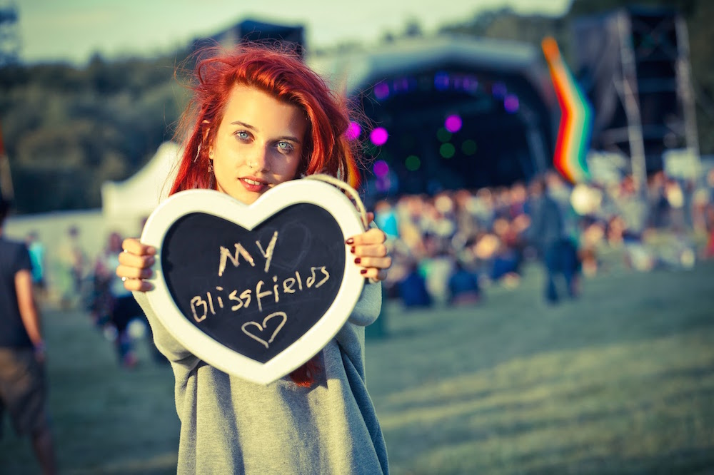 red headed woman holding heart shaped bliss fields sign