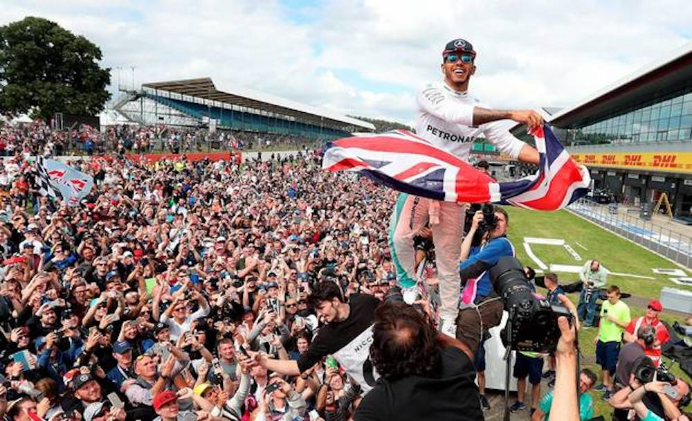 lewis Hamilton waving Union Jack flag to crowd