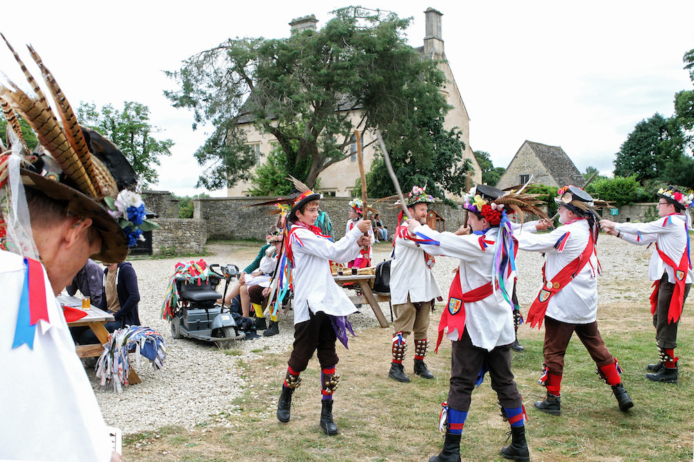 Morris dancers in white shire and feather hats