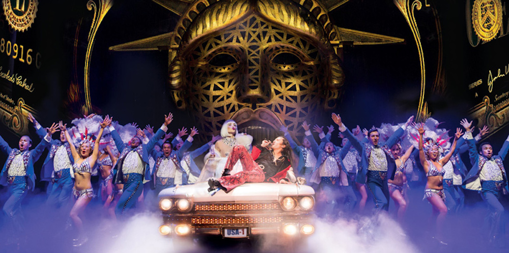 miss Saigon production man singing on car stage of liberty backdrop