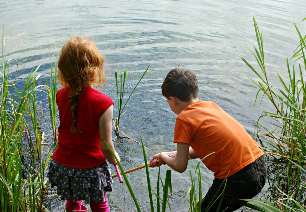 two children pond dipping, a girl in a red top and a boy with an orange top from behind