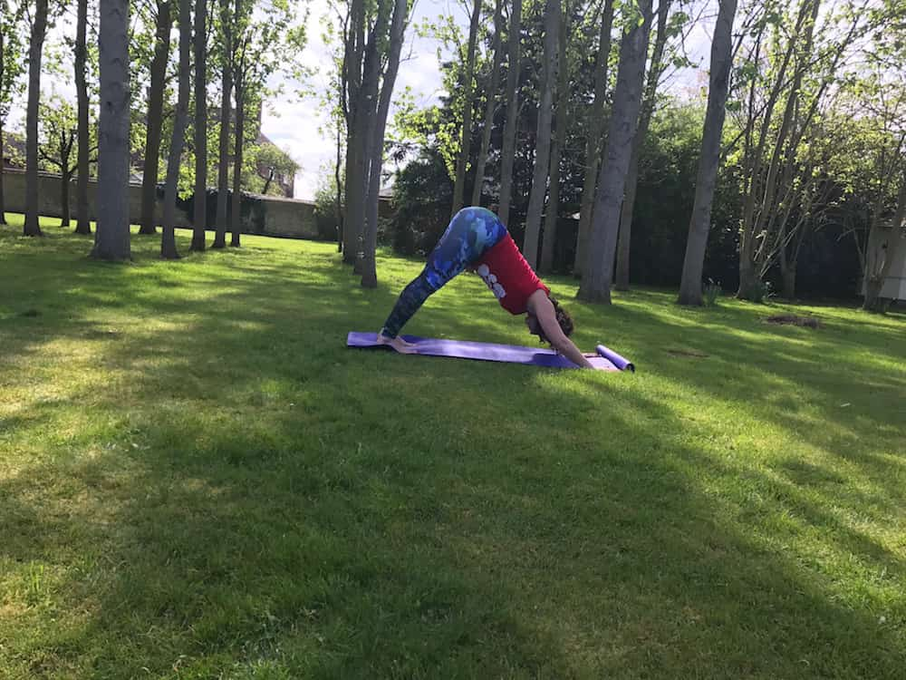 woman in downward dog position in garden