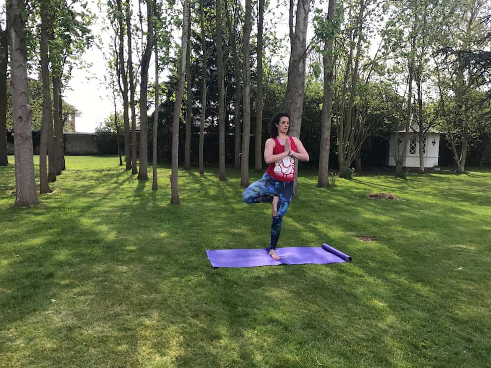woman doing yoga in garden surrounded by trees