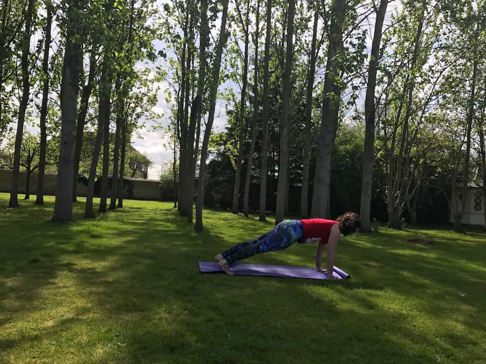 woman doing yoga in garden on purple mat