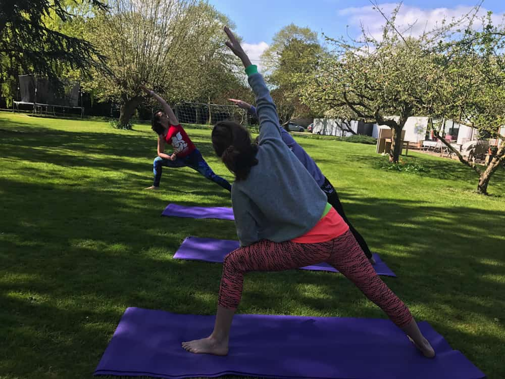 two women copying yoga instructor in garden