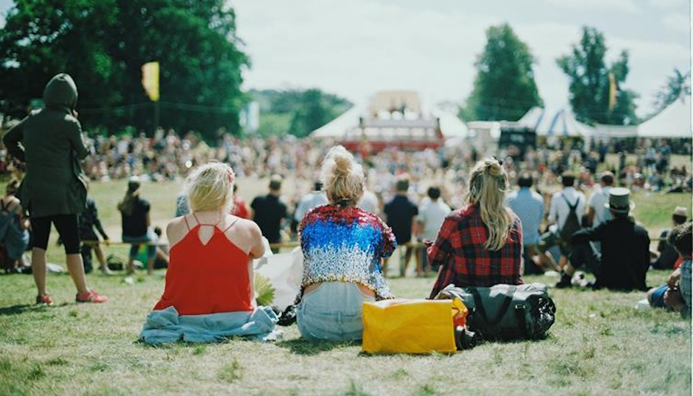 three girls sitting on grass at festival