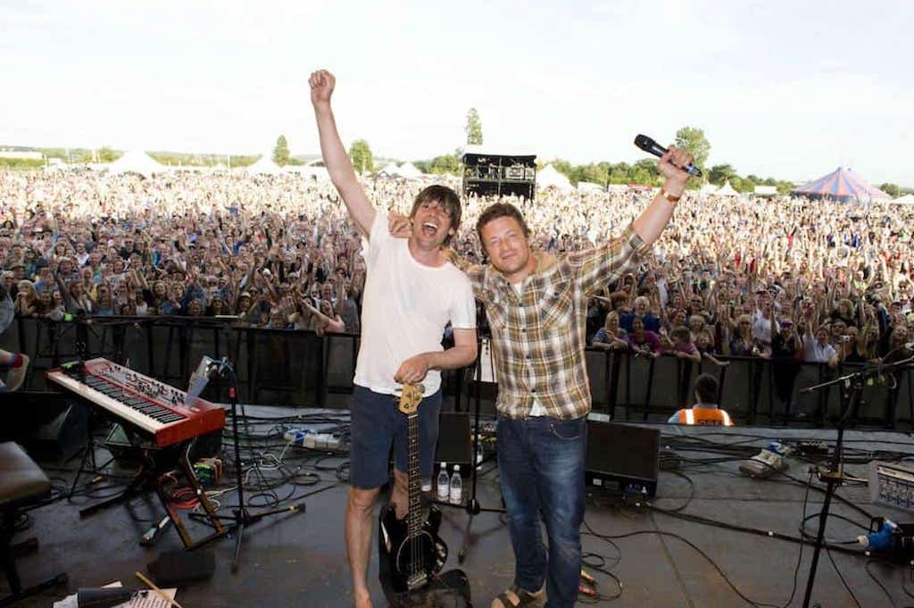 jamie oliver and alex james at big feastival smiling onstage with thousands of fans behind them