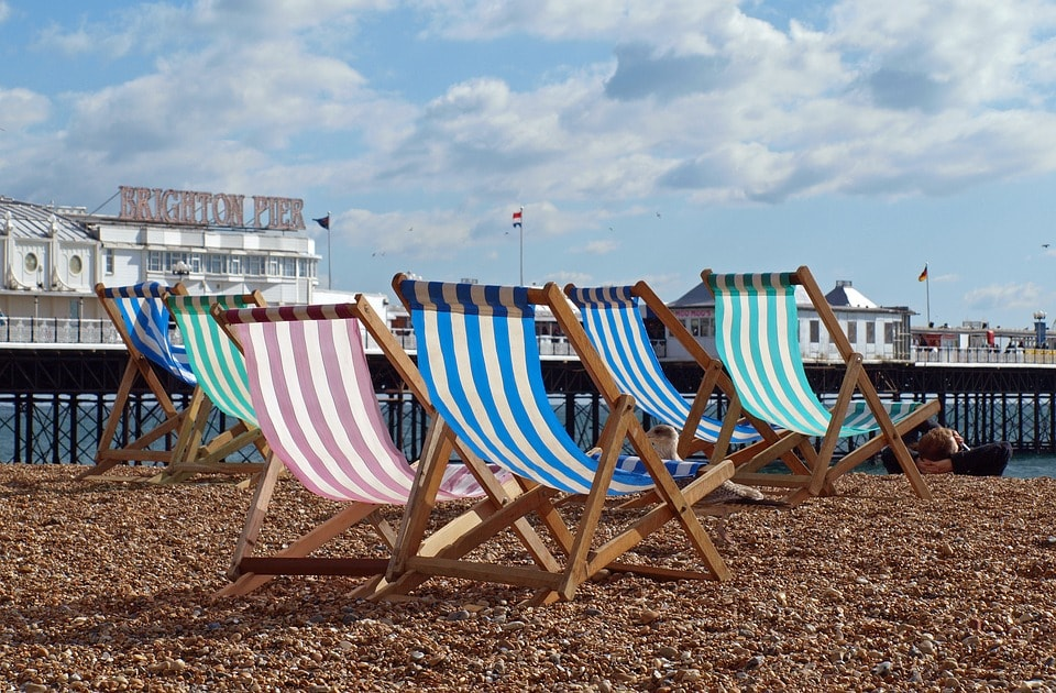 STRIPED DECK CHairs on Bright Beach with pier