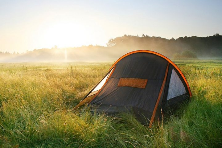 single tent in field sun set