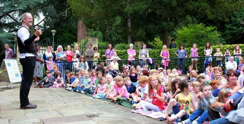 child audience watching man in waistcoat