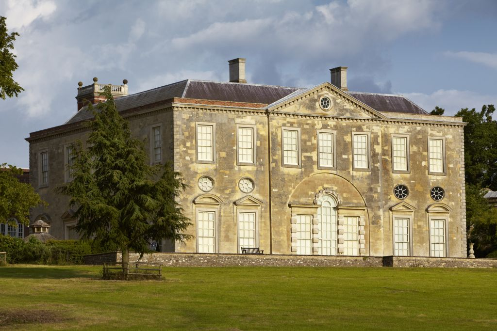 large 18th century house with huge windows overlooking grassland