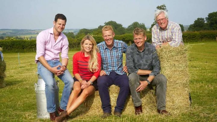 countryfile presenters sitting on a hay bay and smiling