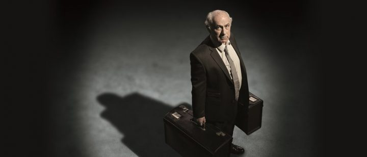 old man in spot light holding suit cases