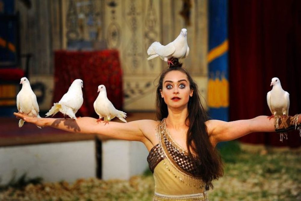 female circus performer with doves on head and arms