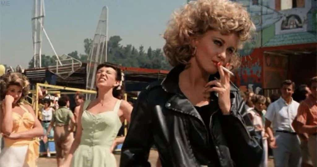 Olivia Newton John smoking a cigarette and wearing a black leather jacket before singing you're the one that I want in grease the movie
