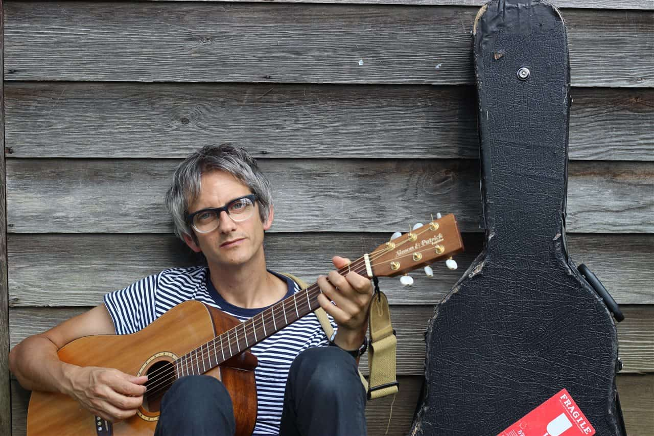 man wearing glasses holding guitar next to guitar case