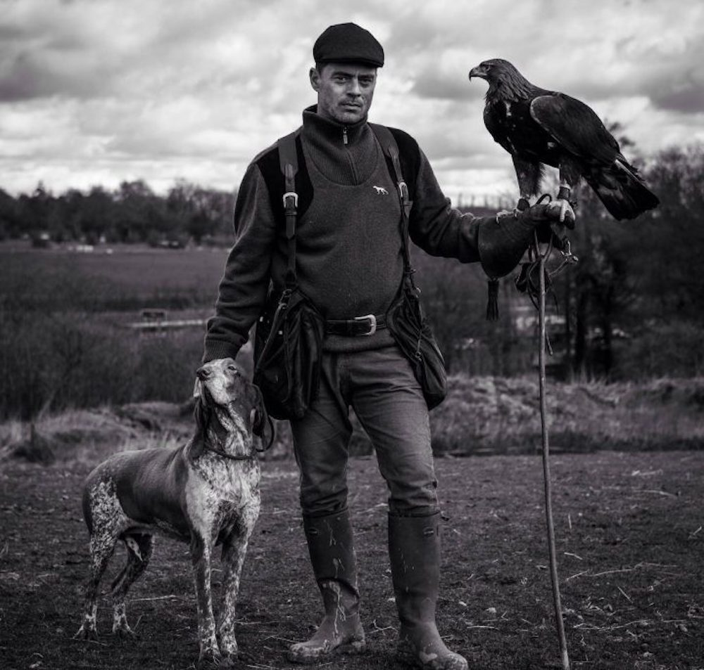 blacka nd white photograph of man dog eagle