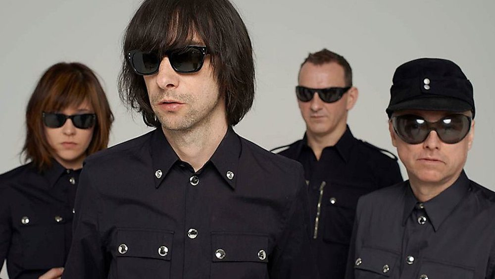 primal scream band in black shirts and sunglasses
