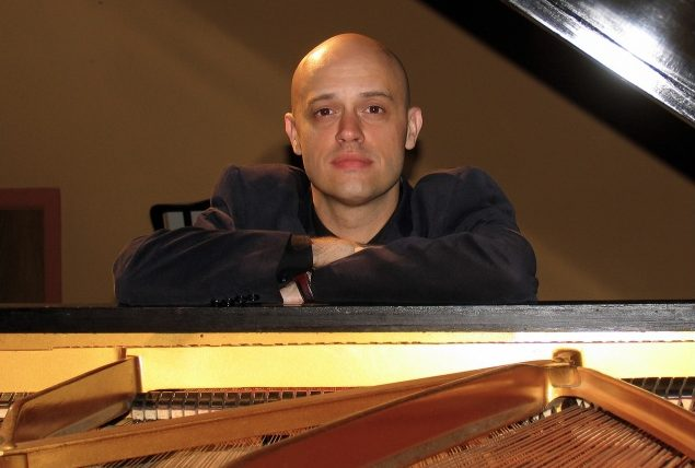 bald man leaning on grand piano