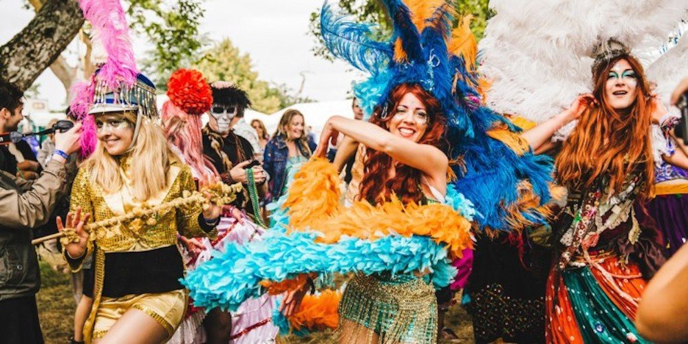 wilderness festival goers in bright costumes dancing