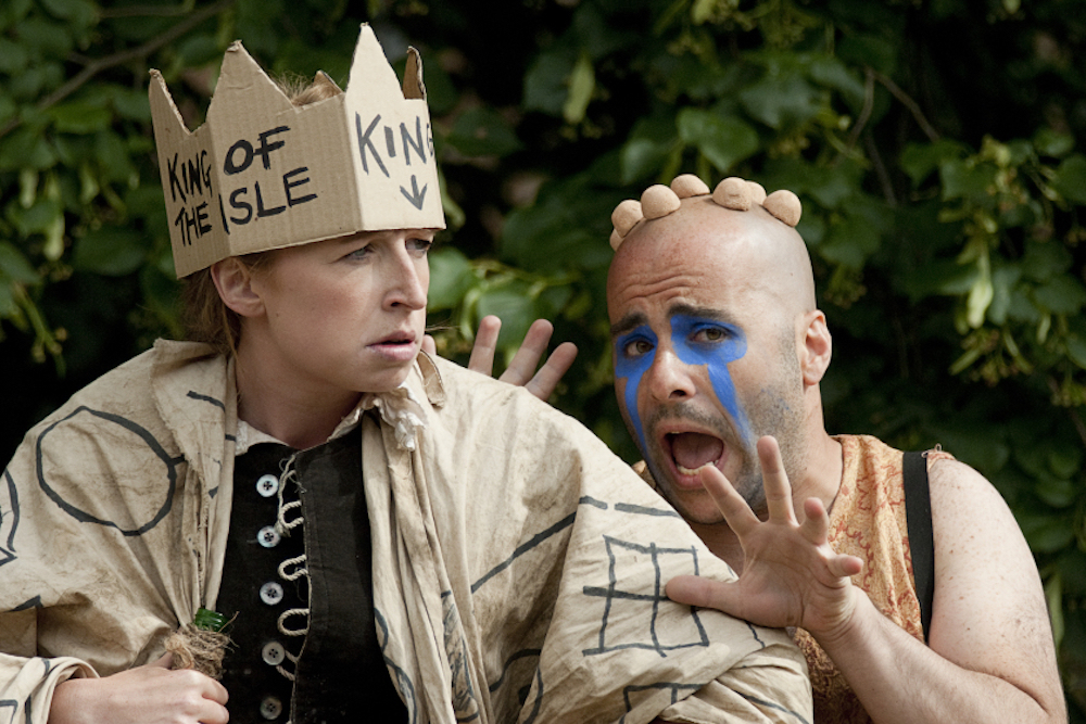 actor in cardboard crown bald actor with blue face paint