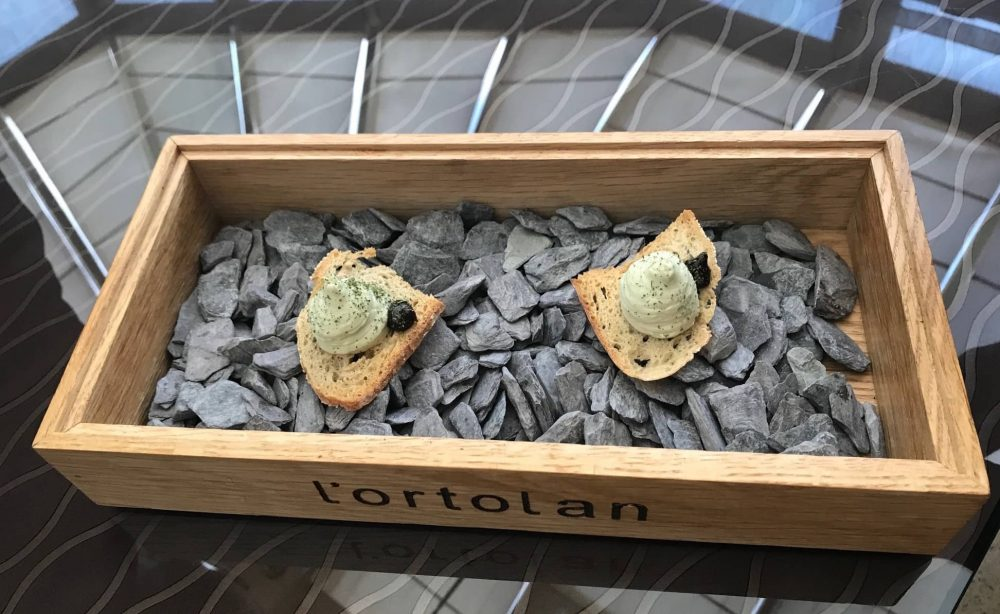 toast with pate in crate of grey stones